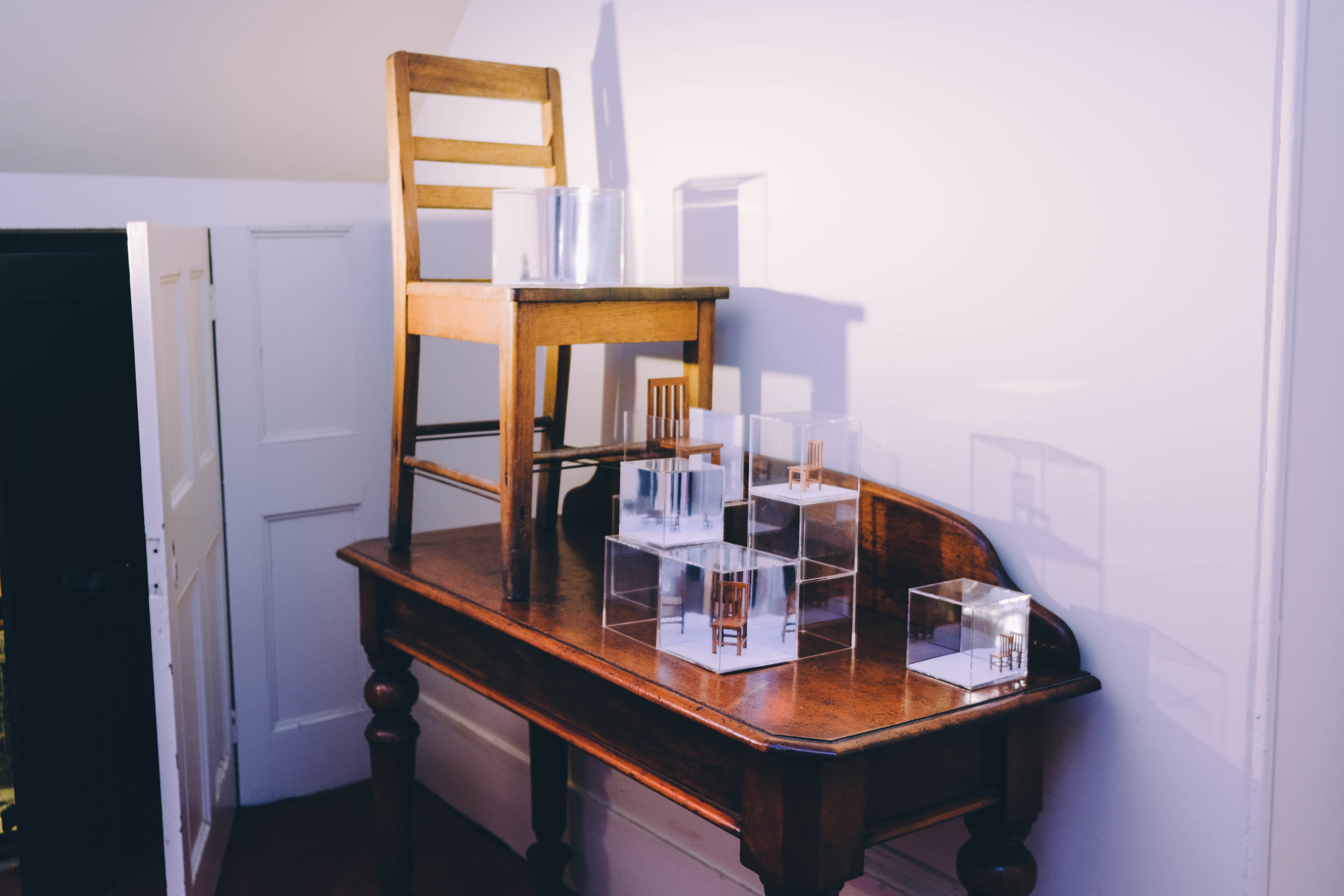 Display of chairs representing scale on table