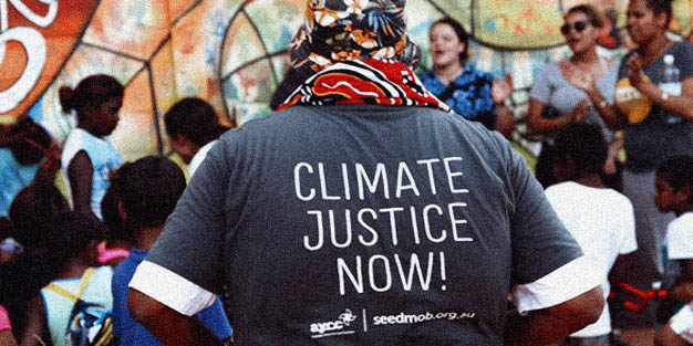 """Back of someone's shirt that says """"CLIMATE JUSTICE NOW!"""""""