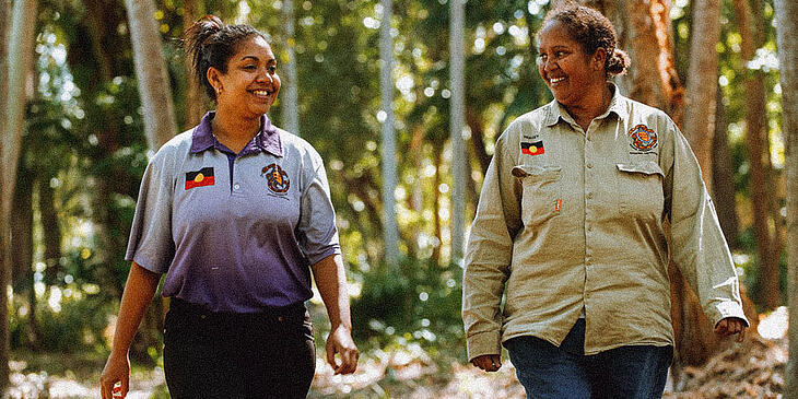 Two women in ranger uniforms walking through a forest and smiling