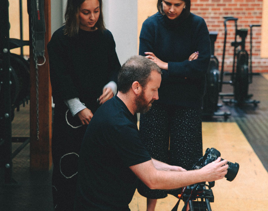 Rikki Bunder using a camera while two students watch